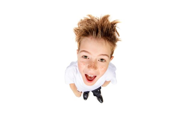 A boy in white t-shirt stares into the camera, he is surprised.