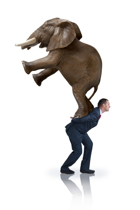 a determined strong businessman carrying an elephant on his back