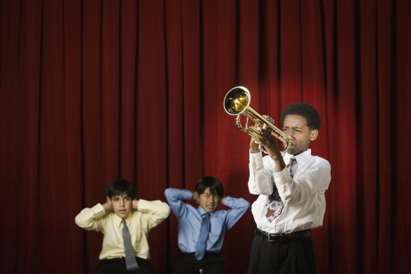 Boy playing trumpet with classmates covering ears