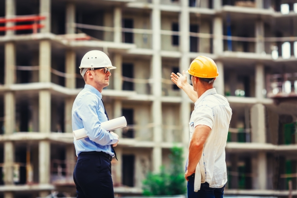 Architect and builder discussing at construction site.