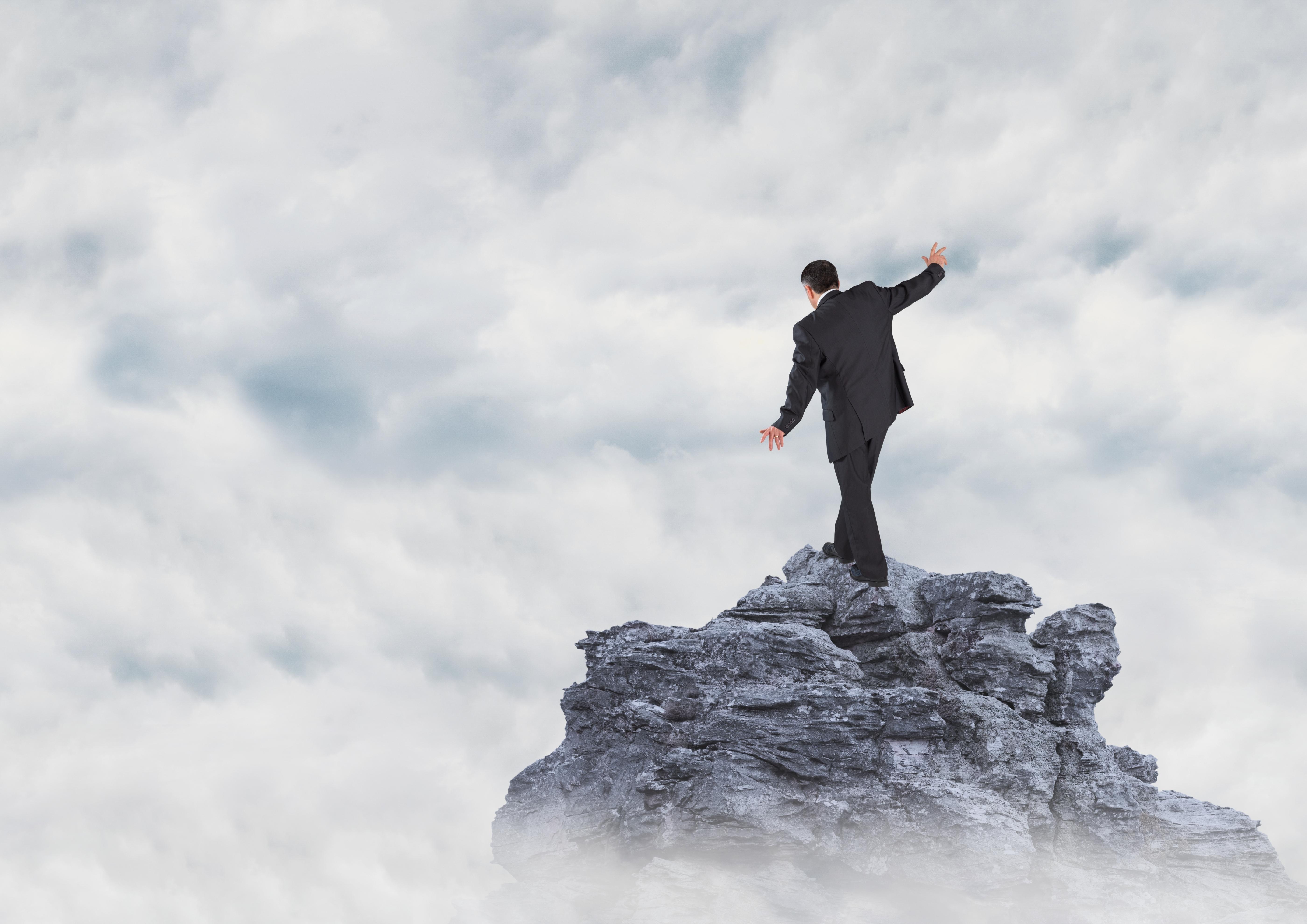 Digital composite of Business man walking up mountain peak in th