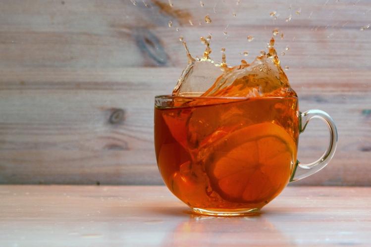 Close Up Transparent Teacup With Black Tea Spilling Over Because
